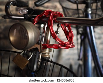 Bicycle handlebars, headlight, red chain with padlock.