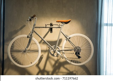 Bicycle hanged on loft cement wall in small space apartment.