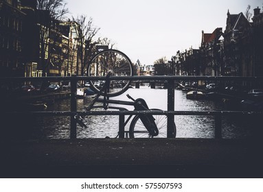 Bicycle hanging on bridge tied to railings over canal in Amsterdam, dark vignette effect