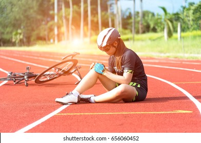 Bicycle injury accident. Biker holding her knee and legs in summer day. Cyclist Concept