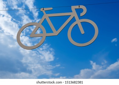 Bicycle lane, grey symbol of a bike hanging from a cable on a blue sky with clouds. Italy