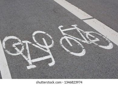 Bicycle lane or path with white bike symbol on grey road asphalt.