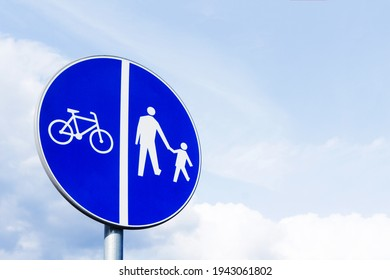 Bicycle lane and pavement next to each other. Recreation walk and cycle path road sign. Round blue information sign. Ubran area road safe to walk.