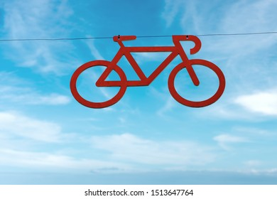 Bicycle lane, red symbol of a bike hanging from a cable on a blue sky with clouds. Italy