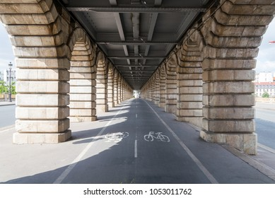 "Bicycle lanes, Bike lanes, pedestrian way under railway metro line over "" Pont de Bercy "" bridge, which cross Seine river in Paris, France"