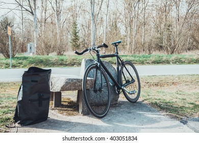 Bicycle leaning up against a stone bench and table alongside a backpack at the roadside on a rural road