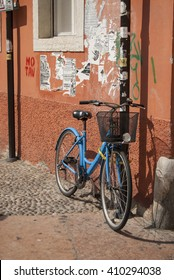 bicycle leaning against a wall, sunny day, Italy