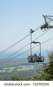 A bicycle lift carrying mountain bikes up a ski hill with the view of the valley below in Collingwood Ontario Canada.