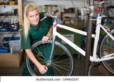 Bicycle mechanic repairing tyre or wheel on bike in a workshop
