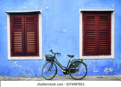 Bicycle with metal basket parked in front of an old wall of a house with flaked Blue plaster and big widows with Red shutters