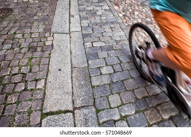 Bicycle moving fast with motion blur on an old cobblestone street. View is looking down, focus is on the stones, movement is blurred.