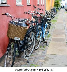 Bicycle near the wall of old building in Copenhagen, Denmark. Copenhagen style, European street, Denmark bicycle with basket