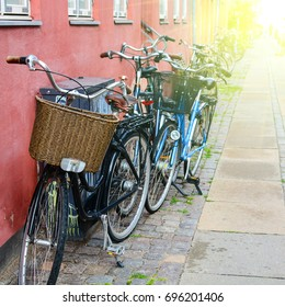 Bicycle near the wall of old building in Copenhagen, Denmark. Copenhagen style, European street. Denmark bicycle with basket and sunshine