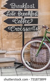 Bicycle near a wooden barrel and pointers on which is written breakfast, coffee, croissants on the street