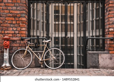 Bicycle next to the fire hydrant leaned on the wall of the grating old red brick building. The streets on Copenhagen in Denmark. Focused on building.