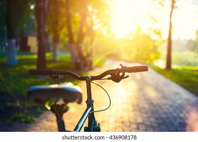 Bicycle on a blurred background of city park at sunset pastel colors during summer.
