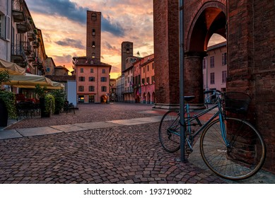 Bicycle on cobblestone town square surrounded by old houses and medieval towers under beautiful evening sky in Alba, Piedmont, Northern Italy.
