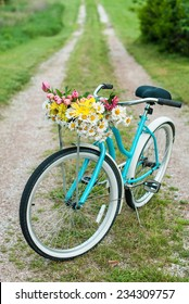 Bicycle on countyside road and a basket of spring flowers with room for copy space.