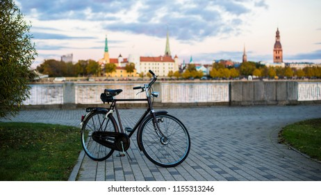 A bicycle on the promenade of the Daugava river at sunset. Old Town of Riga, Latvia in the background