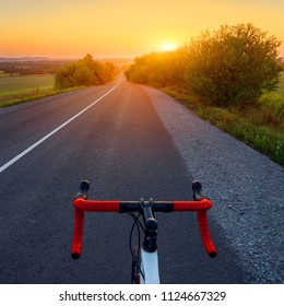 Bicycle on a road. Beautiful sunset landscape with road bike