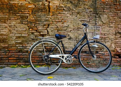 Bicycle on roadside with vintage brick wall background