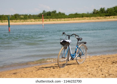 bicycle on the sandy shore at the mouth of the river Livenza, Bibione, Veneto, Italy