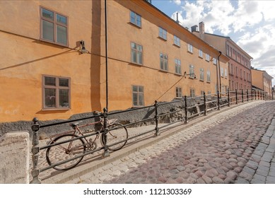 Bicycle on street with cobbled stones, parked between colorful historical houses. Old area of Stockholm, Sweden