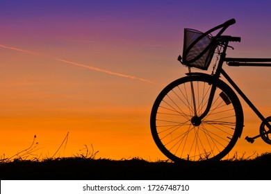 Bicycle in a park at sunset backlit