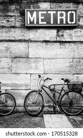 Bicycle parked against a stone block wall under a French metro subway sign. Black and white image. Copy space.