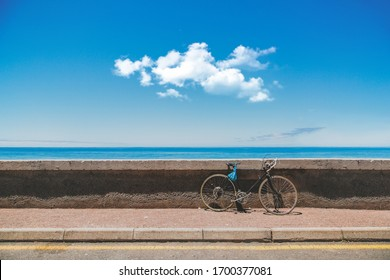 A bicycle parked near the stone border with the sea in the background