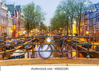 Bicycle parked on a bridge in Amsterdam at night,  Netherlands