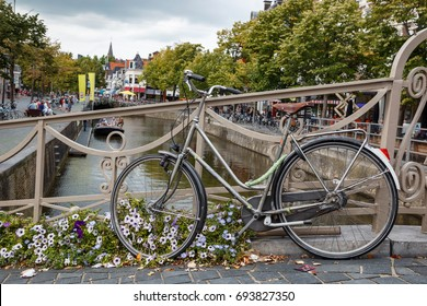 Bicycle parked on bridge in centre of old town leeuwarden in friesland with boniface church in the background.