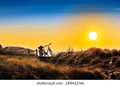 Bicycle parked on the wooden boardwalk over the coastal dune at sunset in Arousa Island