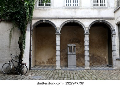 A bicycle is parked outside an old courtyard in Antwerp, Belgium
