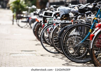 Bicycle parking lot in the city street of Amsterdam. Many different bikes locked on metal holder. Healthy urbant transport in Netherlands.