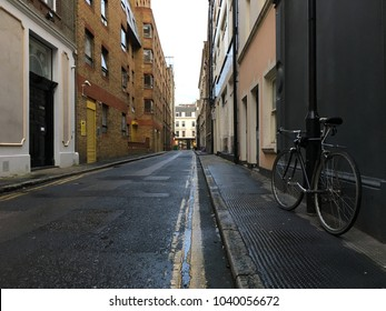 Bicycle parking locked with the black lamp pole on pavement pedestrian quiet road street in London England