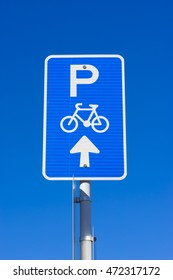 Bicycle parking sign showing parking spaces ahead for bicycles against the blue sky