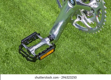 Bicycle pedal with a backdrop of artificial grass.