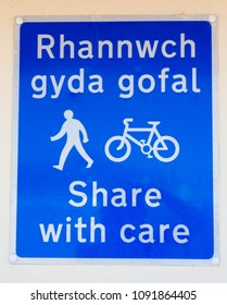 Bicycle and pedestrian share with care route sign in English and Welsh.