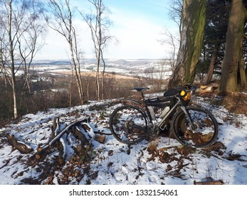 Bicycle propped against a tree in a snowy winter lanscape.