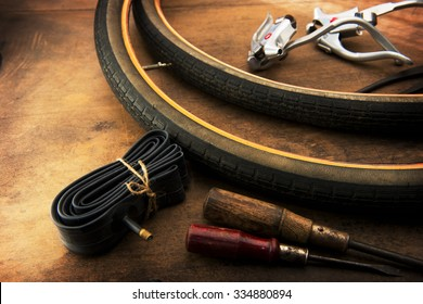 Bicycle repair. Repairing or changing a tire or wheel of an bicycle. Old bicycle wheels on a grungy work desk with inner tube and well used tools and bicycle parts.