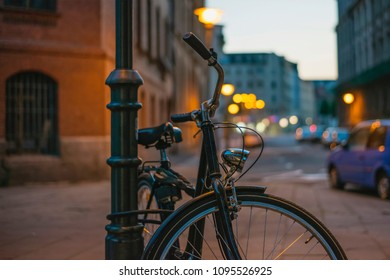 Bicycle in retro style fastened to a post in the dark on a street in a European city