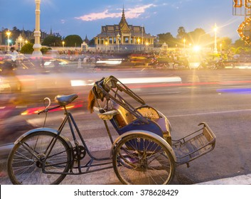 A bicycle rickshaw is parked in front of Phnom Penh Royal Palace in Cambodia capital city. The traffic is captured with long exposure to give contrast with the immobile vehicle.