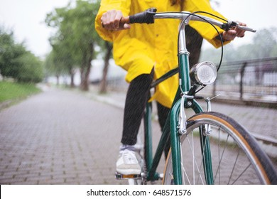 Bicycle ride in the rain. Close up of bicycle rider wearing yellow raincoat