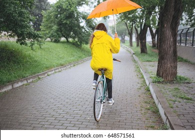 Bicycle ride in the rain. Woman in raincoat riding bicycle and holding umbrella