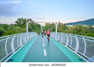 "Bicycle riders riding on bicycle bridge (called ""Freedom bridge"") connecting two countries Slovakia and Austria (Bratislava, SLOVAKIA)"