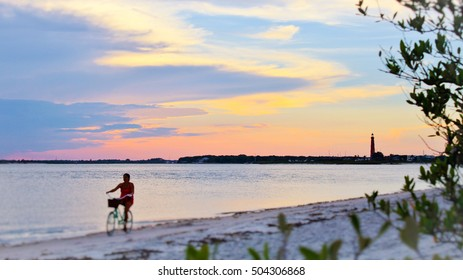Bicycle rides by as Sun Sets over Lighthouse