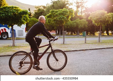 bicycle riding male in black sportswear and sunglasses