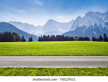 Bicycle road in alps. Landscape with green meadow and mountains on background.