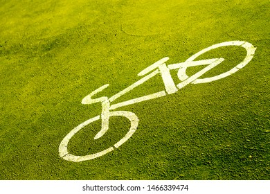 bicycle sign stencilled with white paint on a bright green pavement indicating a designated area for cycling